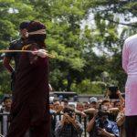 Algojo melakukan eksekusi cambuk terhadap pelanggar syariat Islam di halaman Masjid Syuhada Lamgugop, Banda Aceh