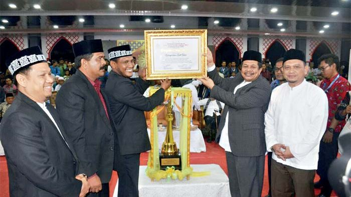 SEKDA Aceh, Dermawan (dua kanan) di dampingi Kepala DSI Aceh Dr. Munawar A Djalil MA (Pertama Kanan), menyerahkan piala bergilir kepada Bupati Aceh Timur, H Hasballah bin HM Thaib, setelah kafilah tuan rumah tampil sebagai juara umum MTQ Ke-33 Aceh Tahun 2017. Penyerahan itu berlangsung pada penutupan even tersebut di Lapangan Upacara Pemkab Aceh Timur, Idi Rayeuk, Sabtu (25/11) malam.