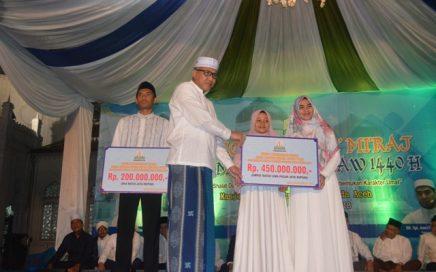 Plt Gubernur Aceh, Nova Iriansyah (dua dari kiri). menyerahkan bonus secara simbolis kepada juara MTQN pada peringatan Isra Mikraj di halman Masjid Raya Baiturrahman, Banda Aceh, Selasa (2/4) malam.